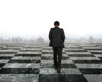 Rear view businessman walking on chessboard royalty free stock images