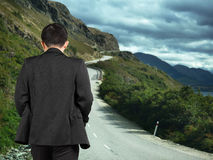 Rear view businessman walking on mountain road with cloudy sky Stock Images