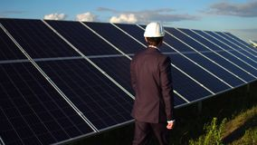 Rear view of businessman walking at solar energy station. Man in busibess suit controling installation of solar panels stock video footage