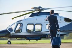 Rear View Of Businessman Walking Towards Helicopter Whilst Talki stock photography