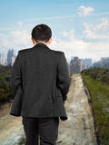 Rear view businessman walking on trail to city with cityscape Stock Photo