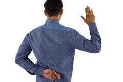 Rear view of businessman waving hand with crossed fingers. While standing against white background Stock Photos