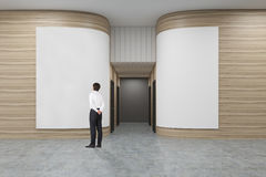Rear view of a businessman in a white shirt looking at a poster in an office hall with rounded wooden walls. Rows of doors are leading to an elevator. 3d Royalty Free Stock Images