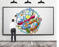 A rear view of businessman who is drawing a colourful business development flowchart on the concrete wall. There are three ceiling Royalty Free Stock Photos