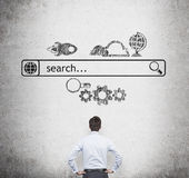 Rear view of the businessman who is looking at the wall with the drawn internet search bar and different icons. Stock Photo