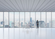Rear view of the businessman who looks out the window in New York's panoramic office. Royalty Free Stock Images