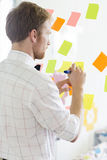 Rear view of businessman writing on sticky paper at creative office Royalty Free Stock Photos