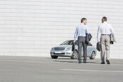 Rear view of businessmen carrying briefcases while walking towards car on street Royalty Free Stock Photo