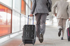 Rear view of businessmen with luggage running on railroad platform Royalty Free Stock Images