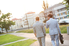 Rear view of businessmen walking at park on sunny day Royalty Free Stock Images