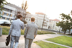 Rear view of businessmen walking at park on sunny day Stock Photo
