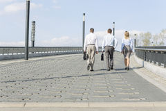 Rear view of businesspeople walking on bridge Stock Photo