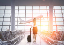 Rear view of businesswoman in airport, toned Royalty Free Stock Image