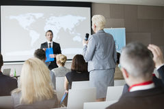 Rear view of businesswoman answering questions during seminar Stock Photography