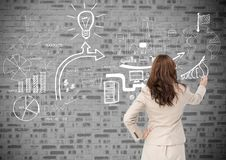 Rear view of businesswoman drawing icons on brick wall stock illustration