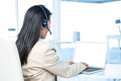 Rear view of businesswoman with headset using laptop Stock Image