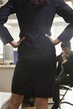 Rear view of businesswoman with her hands on hips confronting a coworker Royalty Free Stock Photo