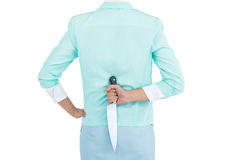Rear view of businesswoman hiding knife in her back Royalty Free Stock Photography