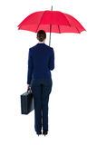 Rear view of businesswoman holding red umbrella and briefcase Royalty Free Stock Images