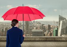 Rear view of businesswoman holding red umbrella while looking at city Royalty Free Stock Photo