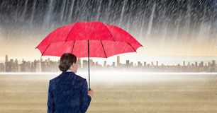 Rear view of businesswoman holding red umbrella standing in digital composite image of rain Royalty Free Stock Image