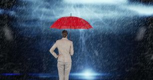 Rear view of businesswoman holding red umbrella standing in rain Stock Photos
