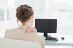 Rear view of businesswoman with neck pain in office Royalty Free Stock Photography