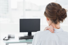 Rear view of a businesswoman with neck pain in office Royalty Free Stock Photography