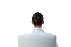 Rear view of businesswoman sitting on chair. Against white background Stock Images