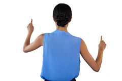 Rear view of businesswoman in sleeveless clothing pointing on interface. Against white background Royalty Free Stock Images