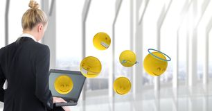 Rear view of businesswoman using laptop while emojis flying in office. Digital composite of Rear view of businesswoman using laptop while emojis flying in office Royalty Free Stock Images