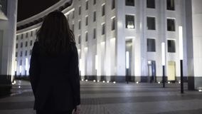 Rear view of a businesswoman walking in a night city street