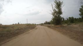 Rear view of car driving along a rural dirt road stock video