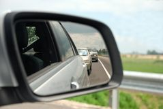 Rear view car mirror. Rear view mirror reflecting a line of cars behind Royalty Free Stock Images