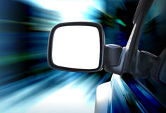 Rear View Car Mirror Driving with Speed. A closeup of a blank white rear view mirror on a car driving fast on a road. There is a zoom effect. Add your image or Royalty Free Stock Photos