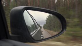 Rear view of car mirror on the road in nature on a cloudy day. Driving through pine forest landscape.  stock video footage