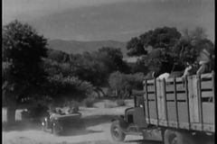 Rear view of a caravan of cars and trucks driving on a dirt road stock video