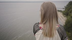 Rear view at carefree caucasian woman wearing long summer fashion dress standing on the field on the background of a. Rear view at awe caucasian woman wearing stock video