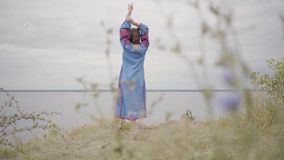 Rear view at carefree caucasian woman wearing long summer fashion dress standing on the field on the background of a. Rear view at awe caucasian woman wearing stock video footage