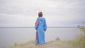 Rear view at carefree caucasian young woman wearing long summer fashion dress standing on the field on the background of. Rear view at awe caucasian woman stock video footage