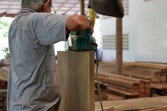 Rear view of carpenter using belt sander in carpentry workshop Stock Image