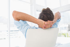Rear view of a casual man resting with hands behind head in office. Rear view of a relaxed casual young man resting with hands behind head in a bright office stock images