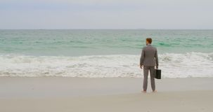 Rear view of Caucasian Businessman standing with briefcase on the beach 4k stock video footage