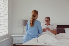 Female doctor talking to disabled active senior man about his hearing aid in bed in bedroom. Rear view of Caucasian female doctor talking to disabled active stock photography