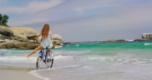 Rear view of Caucasian woman riding a bicycle on the beach 4k