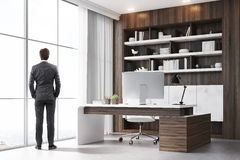 Rear view of CEO in his dark wood office. Rear view of a company CEO standing in his dark wood office with a bookcase, a massive table and a computer. 3d royalty free stock images