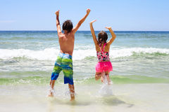 Rear view of cheerful children jumping in water. Rear view of two cheerful little children jumping together in water with arms raised. Siblings or friends having Royalty Free Stock Photos