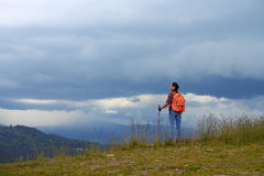 Mid shot of cheerful female standing on mountain with hiking pol Royalty Free Stock Photography