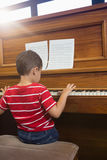 Rear view of cheerful friend playing piano while sitting in classroom Royalty Free Stock Image