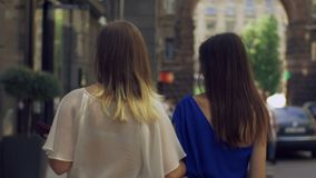 Happy shopping women walking along city street. Rear view of cheerful long hair women walking along shopping street and chatting during shopping together stock footage